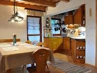 Chata - jídelní stůl a kuchyň v přízemí