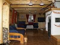 Obývací část přízemí s kamny - pronájem chalupy Velké Karlovice