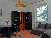 Obyvácí pokoj s rozkládací sedačkou a stolem