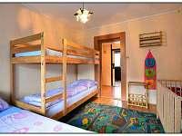 Ložnice s dětskou postýlkou, hracím kobercem a košem plným hraček - chata k pronájmu Visalaje