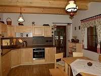 Kuchyně s jídelním stolem a přímým vstupem na venkovní terasu - chalupa k pronájmu Velké Karlovice