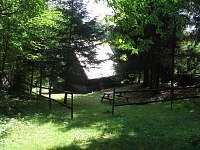 Pohled na chatu, posezení a ohniště z lesa - k pronájmu Trojanovice
