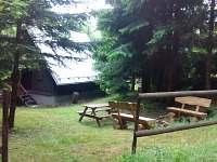 Pohled na chatu, posezení a ohniště z lesa (nové lavice a přístřešek u dveří)