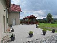Prostorná terasa s pergolou a venkovním posezením