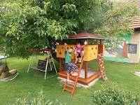 Dětský domeček s pískovištěm ve stínu velkého ořechu.