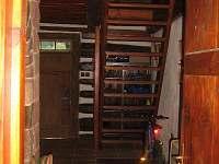 Schody do ložnic v podkroví a hlavní dveře z pohledu od koupelny