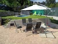 Venkovní posezení pod slunečníkem,dětské pískoviště s hračkami a bazén s lehátky
