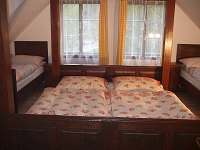 Čtyřlůžkový pokoj s manželskou postelí a s posezením.
