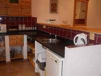 Kuchyňský kout s varnou deskou a myčkou nádobí.