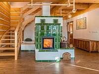 Prostorný obývací pokoj s kachlovými kamny - chalupa k pronájmu Branná