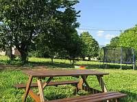 Aprtmány U mlýna, venkovní posezení s trampolínou a pískovištěm v pozadí - apartmán k pronájmu Maršíkov