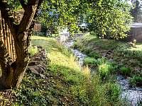 Za plotem protéká hezký potok