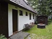 Pohled na bok chaty s lavičkou - chalupa k pronájmu Heřmanovice