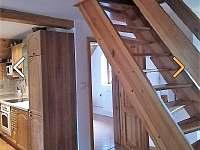 Koupelna s kuchyní a schody nahoru do ložnice.
