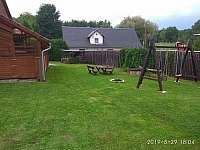 pohled ze zadní části zahrady na houpačky a posezení - chalupa ubytování Domašov