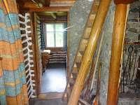 Vstup do kuchyně, místnosti s krbem a příkré schody do ložnice v podkroví