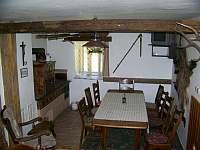 Spol. místnost má kachlová kamna, dva velké stoly, židle, křeslo a televizi