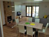 Obývací pokoj s krbem, TV, vstupem do zimní zahrady