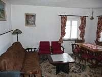Pohled na společenskou místnost s jídelním stolem a pohovkou - pronájem chalupy Nové Losiny