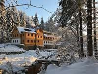 Chata v zimě pohled z lesa přes řeku - Josefův Důl