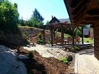 pohled od zadního vchodu na posezení s houpačkou a pískovištěm nad ním