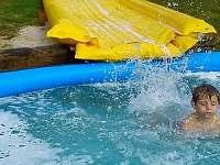 Letní koupání s vodní skluzavkou přímo do bazénu.