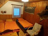 Ložnice se třemi lůžky, skříní, křeslem a stolem se židlemi