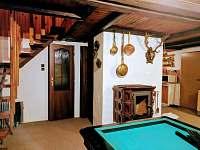 Společenská místnost s posezením, krbovými kamny, televizí a kulečníkem