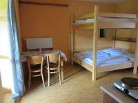 Ubytování Kubínovi_Nová Hlína 32_Malý nový apartmán_postel a stůl - chalupa ubytování Nová Hlína