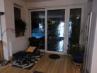 Obývací prostor s venkovní terasou a bazénem