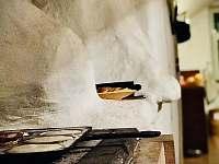 Na peci v obýváku se dá i krásně vařit. Lívanečníky najdete v kuchyni. - pronájem chalupy Stará Vožice