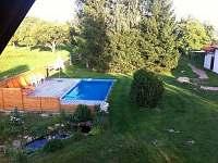 Pohled z balkonu na bazén a zahradu