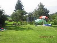 zahrada s trampolínou a malým dětským bazénkem
