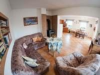 společná místnost s kuchyňkou, posezením, knihovnou a krbem - rekreační dům k pronajmutí Trhové Sviny