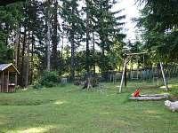 pohled do zahrady s domkem a houpačkou