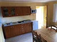 přízemí - vybavená kuchyň, stůl se židlemi a postel - chata ubytování Protivín