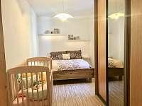 Ložnice v přízemí s postýlkou - rekreační dům k pronajmutí Třeboň