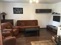 Obývací pokoj s TV a krbem - chata k pronajmutí Suchý