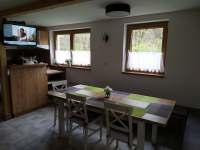 Pohled na jídelní stůl s kuchyní - pronájem chaty Kněždub