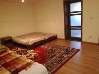 Ve větším pokoji jsou vstupní dveře do menšího pokoje.