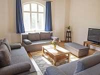 Obývací pokoj s kachlovými kamny - vila k pronajmutí Rajnochovice