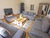 Obývací pokoj s kachlovými kamny - vila k pronájmu Rajnochovice