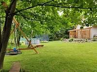 Pohled ze zahrady - houpačky, pískoviště, bazén, trampolína - chalupa k pronajmutí Suchý