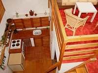 Kuchyňský kout a galerie s přistýlkou v hlavní obytné místnosti