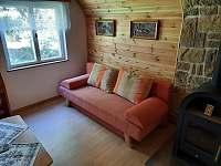 Obývací pokoj (krb, rozkládací sedací souprava, konferenční stolek...) - pronájem chaty Senorady