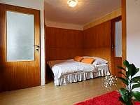 Druhá část oranžového pokoje s velkou postelí - pronájem chaty Milovice