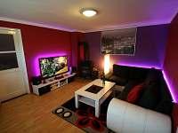 obývací část s rozkládací sedačkou a velikou 3D televizí
