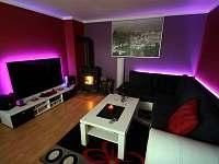 Obývací pokoj s krbem a velikou 3D televizí