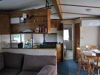 Pohled přes obývak na kuchyni s jídelnou
