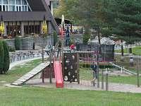 Dětské hřiště, vzadu je restaurace